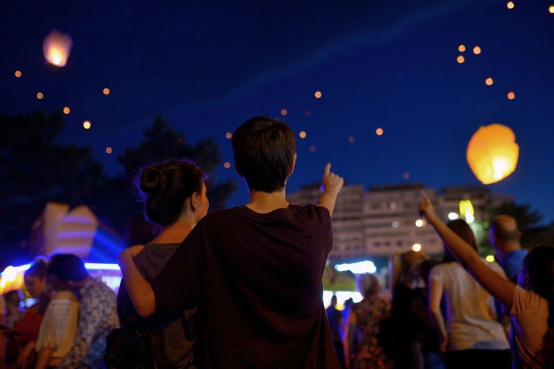 People looking at lit paper lanterns against sky