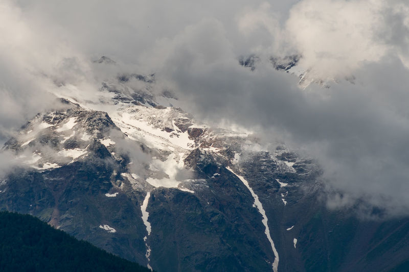 Snow capped peaks of cloud shrouded rocky mountains