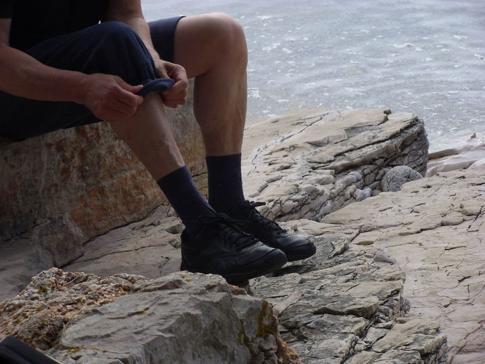 Preparing for hiking by the sea EyeEm Nature Lover EyeEmNewHere Hiking Trekking Beach Body Part Day Human Body Part Human Leg Leisure Activity Lifestyles Nature One Person Outdoors Real People Rock Rock - Object Sea Sitting Solid Water This Is My Skin