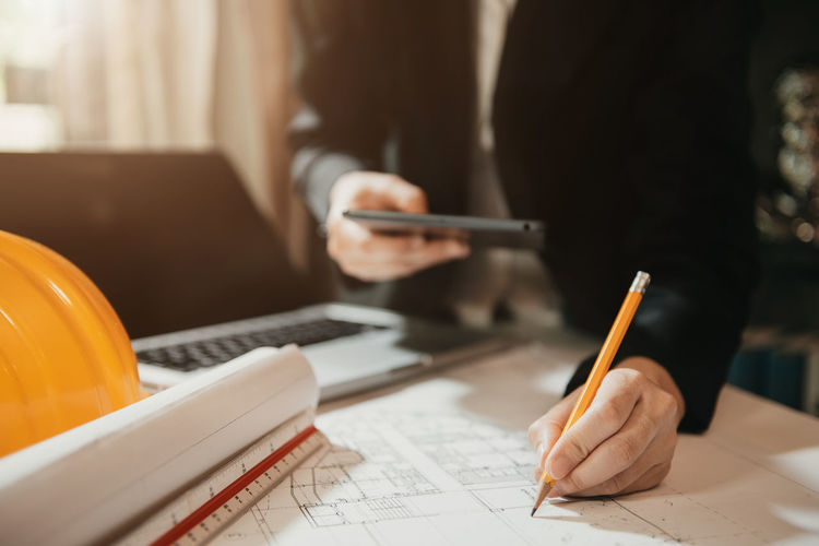 Midsection of man holding paper in pen on table