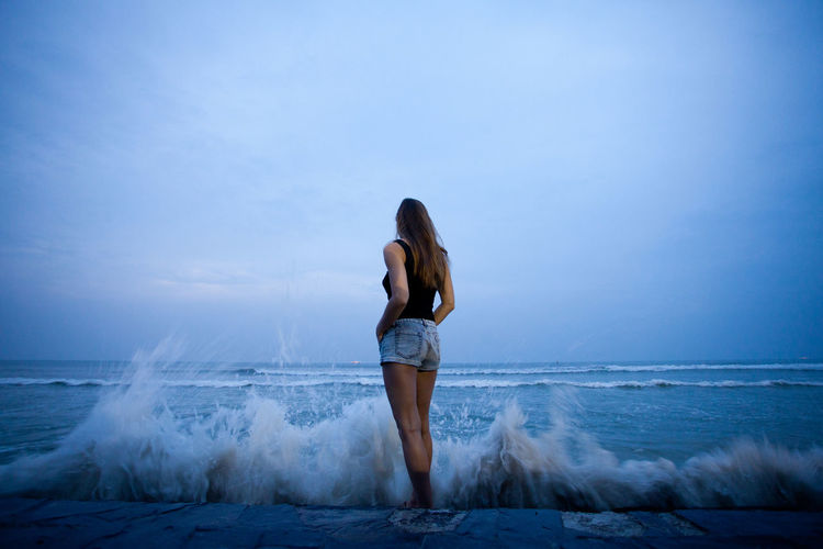 Woman standing back and watching the waves beating against the shore Sea One Person Water Sky Horizon Young Adult Horizon Over Water Motion Wave Standing Beach Adult Land Nature Vacations Women Long Hair Scenics - Nature Hair Hairstyle Beautiful Woman