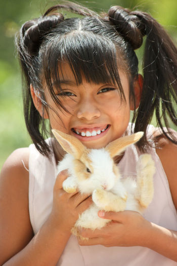 Portrait of cute girl smiling with a rabbit