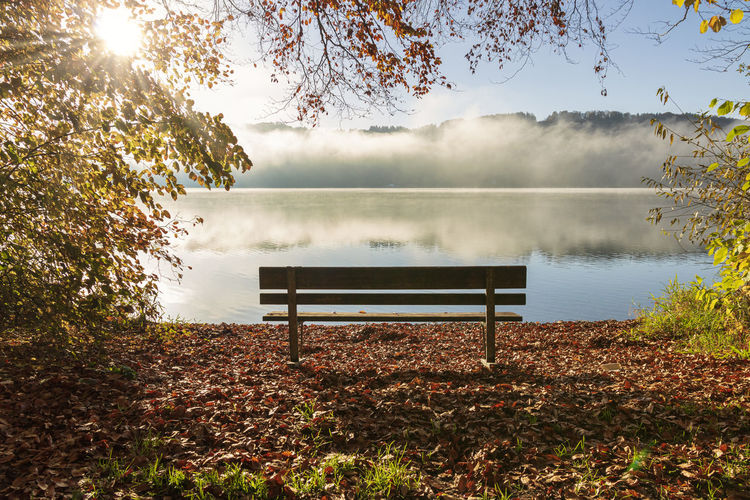 Bench by lake against sky during autumn