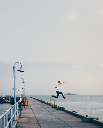 Having faith Beauty In Nature Copy Space Day Flying Full Length Horizon Horizon Over Water Human Arm Incidental People Leisure Activity Lifestyles Nature One Person Pier Railing Real People Scenics - Nature Sea Sky Water