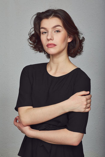 Portrait of beautiful woman standing against wall