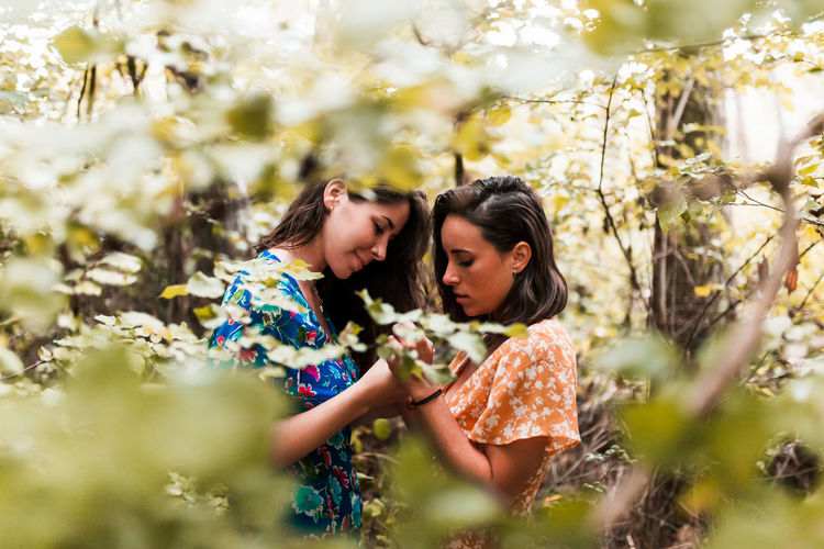Lesbian couple holding hands while standing amidst plants in forest