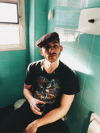 Portrait of young man holding drink while sitting in bathroom at home