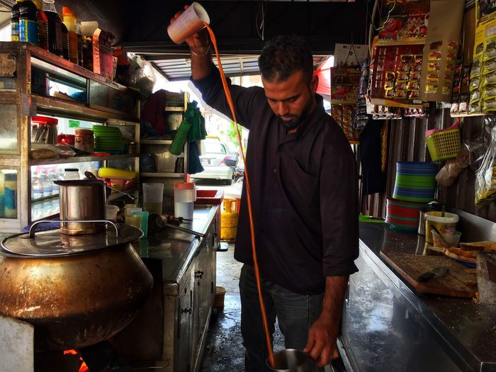 Teh Tarik, a popular tea milk is Malaysia Teh Tarik (Malaysian Pull Tea) Teh Tarik Tea Malaysia Truly Asia Malaysian Food One Person Real People Standing Indoors  Three Quarter Length Occupation Business Men Lifestyles Working Adult Small Business Food And Drink