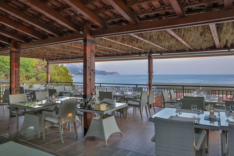 Empty chairs and tables in restaurant by sea