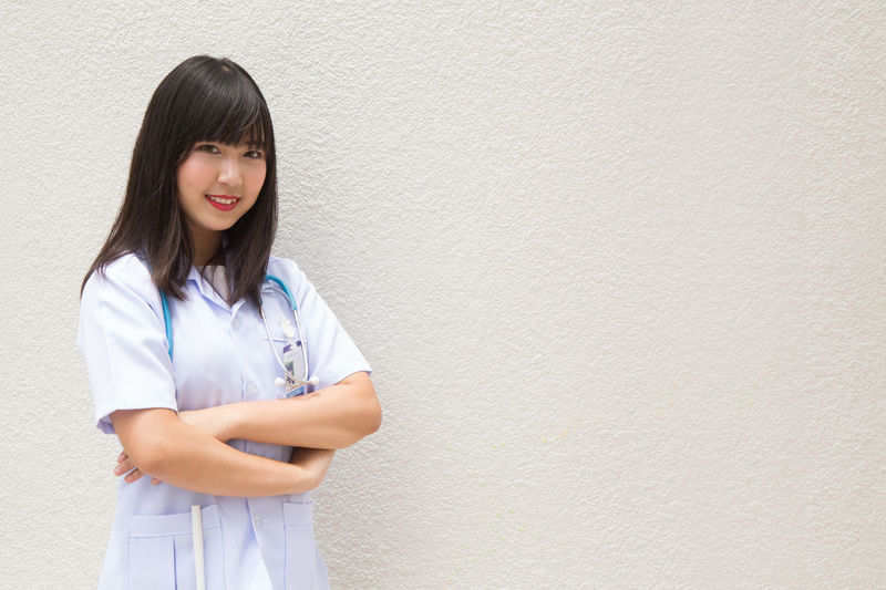 Young Female Doctor Standing Against Wall