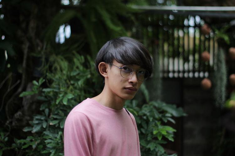 Portrait of teenage boy standing against plants
