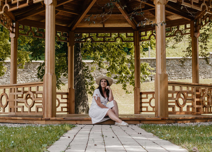 Full length portrait of woman sitting outdoors