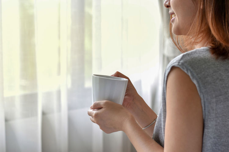 Midsection of smiling woman holding coffee mug against curtain