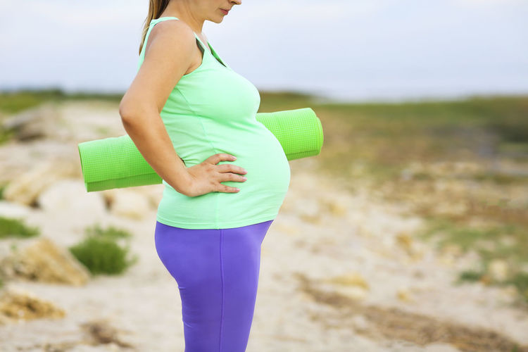Midsection of pregnant woman with exercise mat standing on land