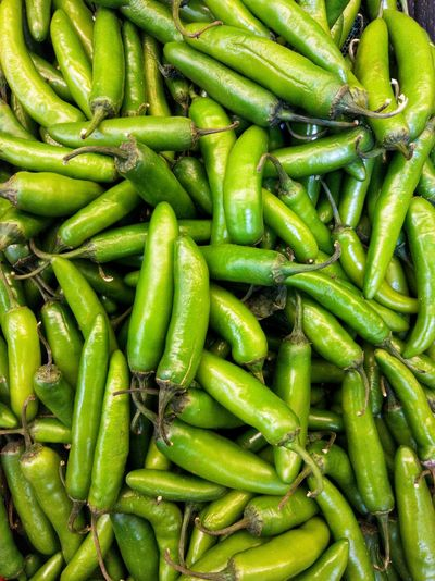 Full frame shot of green chili peppers for sale in market