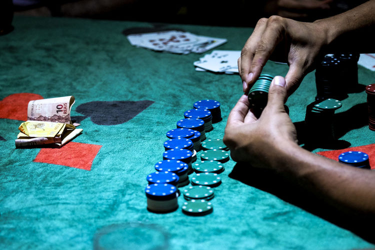 Cropped image of hand playing poker chips on table