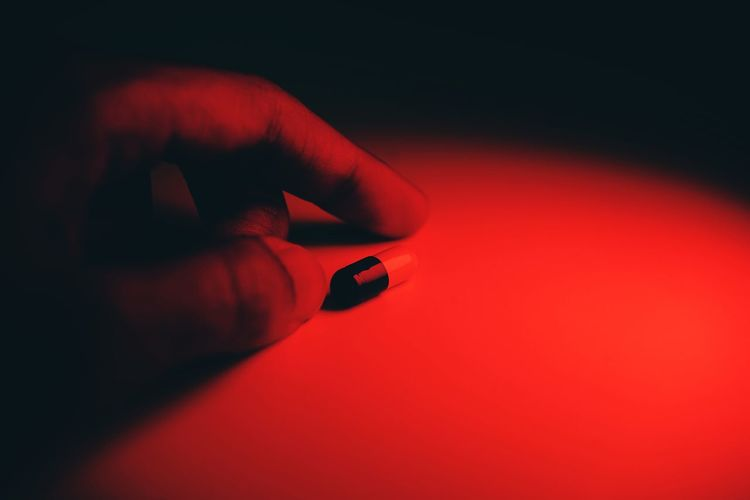 Close-up of human hand holding red light