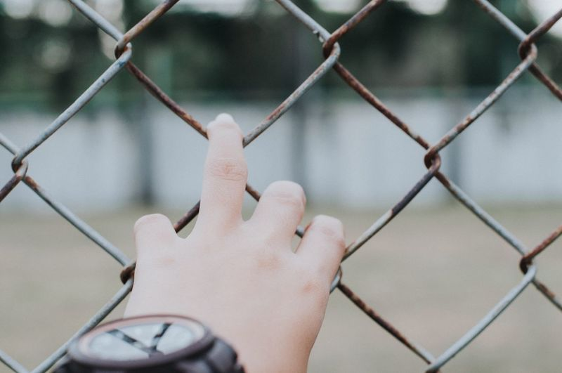 EyeEm Selects Fence Hand Human Body Part Human Hand Chainlink Fence Focus On Foreground Boundary Barrier Safety Real People One Person Security Finger Metal Human Finger Holding Protection Day Close-up Personal Perspective