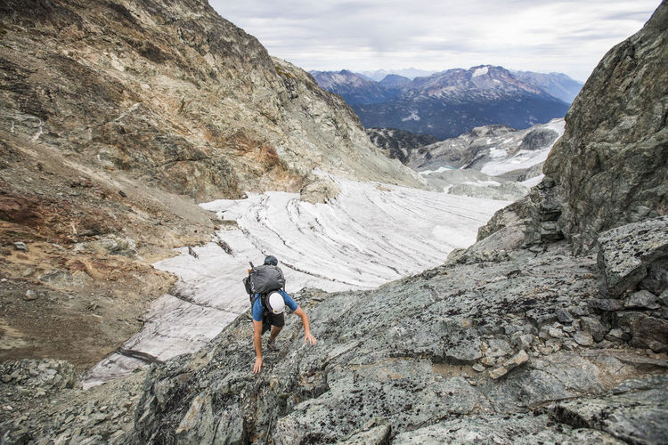 Rear view of man walking on rock in mountains