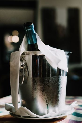 Close-up of wine bottle in container on table