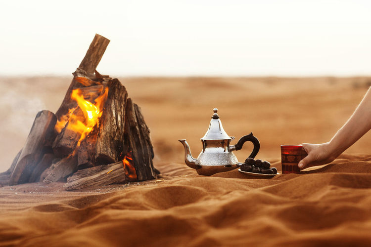 Dates, teapot, cup with tea near the fire in the desert with a beautiful background, ramadan kareem