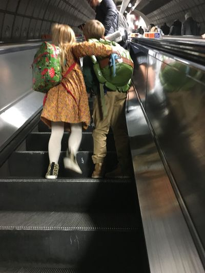 Rear view of people walking on escalator