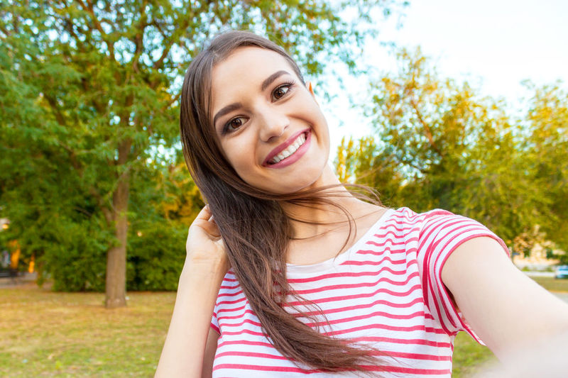 Portrait of smiling beautiful woman standing at park