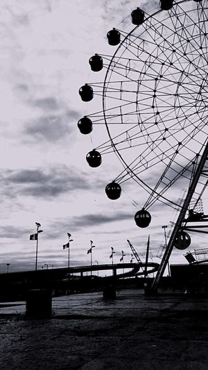 The bridge and the ferris wheel Alone But Not Lonely Walking Around Empty Park Shades Of Gray Flags In The Wind  Silence Lookingup Doingthings Vintage Clouds Sky Architecture No People Day Amusement Park Arts Culture And Entertainment EyeEmNewHere A New Perspective On Life