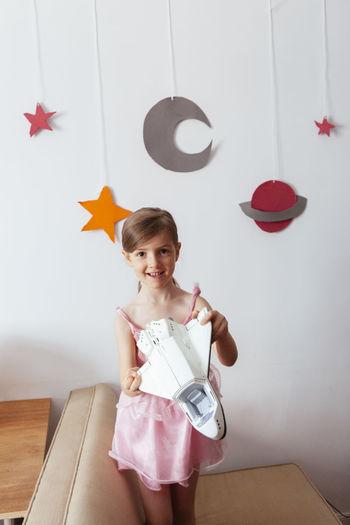 Portrait of smiling girl holding toy against wall at home