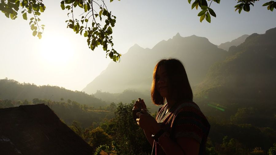 Portrait of woman holding coffee cup by mountains against sky