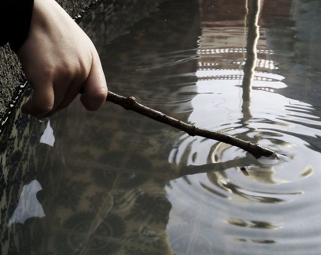 Cropped hand of person dipping stick in water