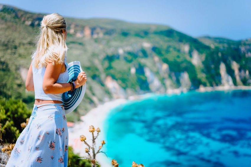 Young woman in front of Petani beach Kefalonia admiring highly excited picturesque panorama of emerald bay of Mediterranean sea and steep coastline island Greece Blue Sea Coastline Come Back Holding Hands Lady Landscape_Collection Tanned Teal AdmireTheView Azure Bay Blond Hair Bright Sun Cyan Female Female Model Greece Petani Saltywater Stay And Wander Sunhat Sunny Day Water Pattern Young Adult Young Women