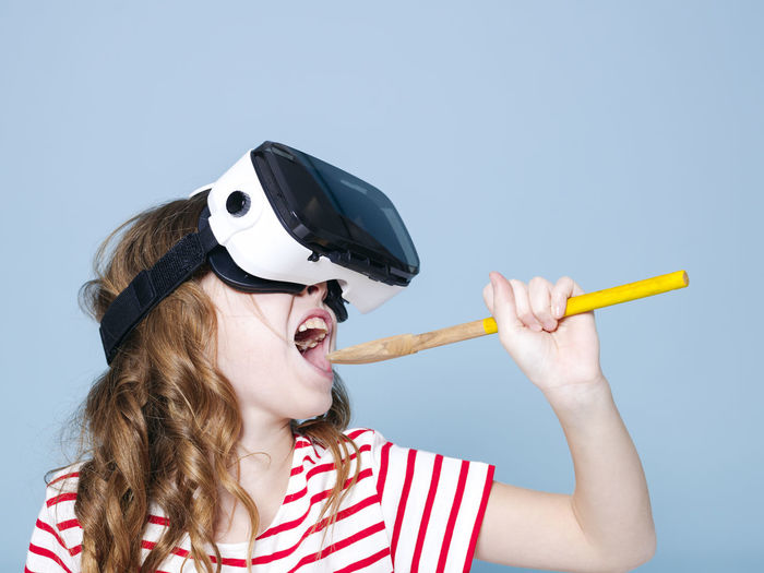 cool and smiling positive girl wearing virtual reality glasses goggles headset is singing with cooking spoon, new generation, concept in front of blue background Leisure Activity One Person Headshot Lifestyles Front View Women Young Adult Hair Young Women Holding Real People Portrait Casual Clothing Hairstyle Fashion Glasses Striped Long Hair Mouth Open Vr Virtual 3D Cooking Spoon Goggles Girl
