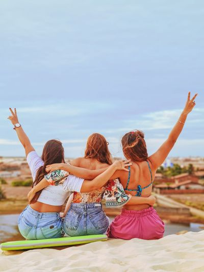 Rear view of cheerful female friends sitting on sand