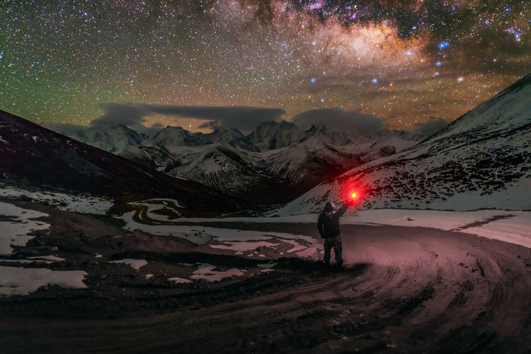 Rear view of person holding flashlight while standing on road at night during winter