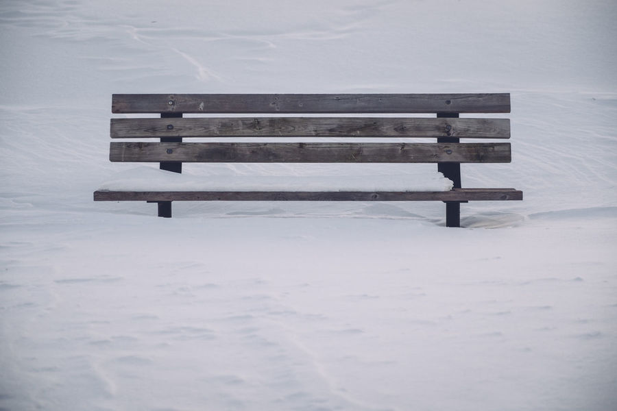 Beauty In Nature Bench Cold Temperature Day Lonely Bench No People Outdoors Simple Simple Photography Simplistic Single Bench Snow Tranquil Scene White Space Winter Wood - Material