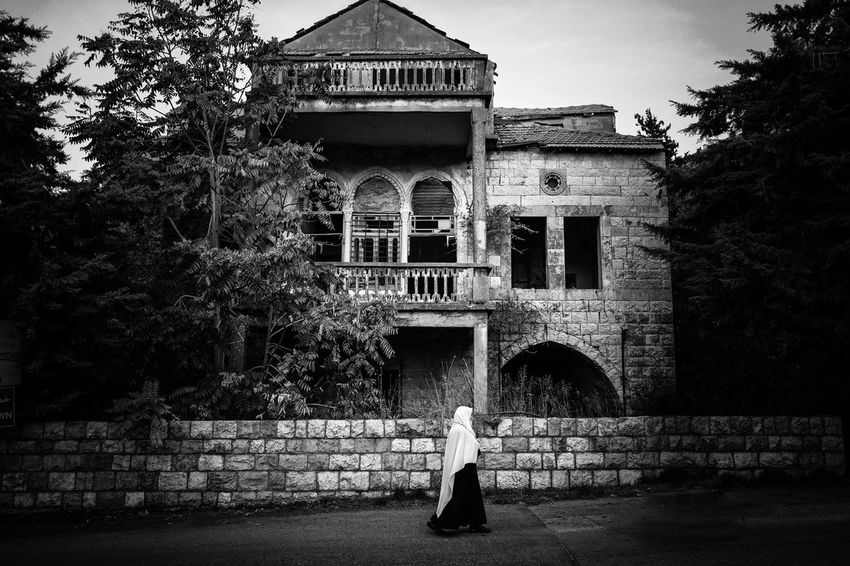 I was mesmerized by this sight. A Druze lady passing by a beautiful but long time abandoned house. The chilling story is that the owners of this house were massacred by Druze neigbohurs during the first bursts of the Lebanese civil war. Today, Druze and Christians live together in peace and harmony as they used to be before the war. Abandoned Places Mount Lebanon War Civil War Lebanese Architecture Druze Jabal House Haunted House Hauntedplaces Hauntedmansion