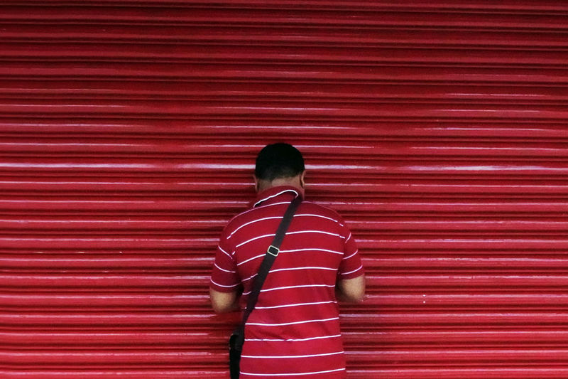 A man in front of the shop door ASIA Colors Shop Door Casual Clothing Clothing Lifestyles One Person Outdoors Pattern Real People Red Same Color Streetphotography Striped
