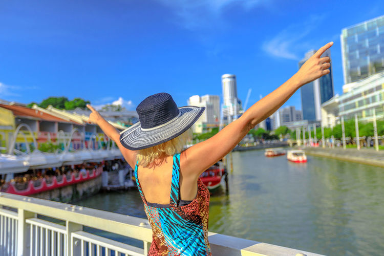 Happy girl backside with hat enjoying at Clarke Quay and Riverside area in Singapore, Southeast Asia. Cruise on Singapore River in sunny day with skyscrapers downtown on background. Singapore Singapore City Woman Tourist Tourist Attraction  Tourist Destination People Girl Females Aerial View Skyline Cityscape Panorama Happy Travel Hat Lifestyle Enjoy Nature Tourism River Clarke Quay Clarke Quay, Singapore Boats Cruise Water One Person Leisure Activity Clothing Women Real People Architecture Lifestyles Built Structure Adult Focus On Foreground Day Rear View Casual Clothing Building Exterior Sun Hat Three Quarter Length Outdoors Hairstyle Human Arm