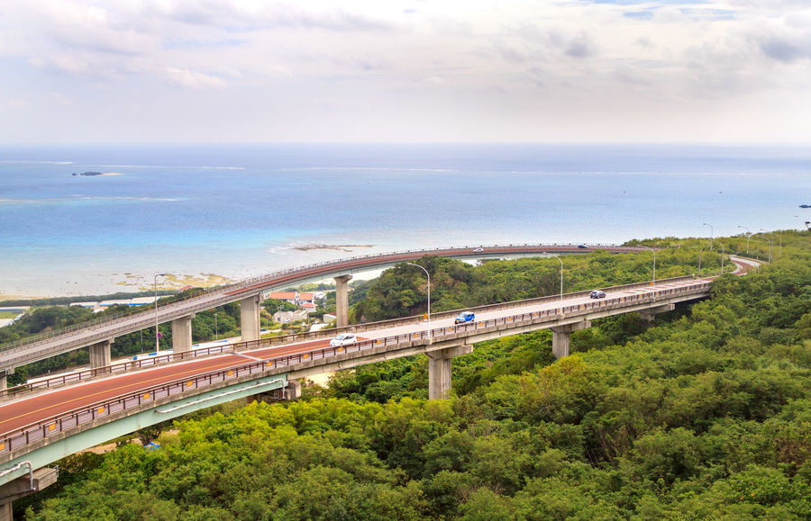 Highway on a hill with the blue ocean in the background Architecture Bridge Bridge - Man Made Structure Built Structure Cloud - Sky Connection Day High Angle View Mode Of Transportation Multiple Lane Highway Nature No People Outdoors Plant Rail Transportation Road Sky Train Train - Vehicle Transportation Tree Water