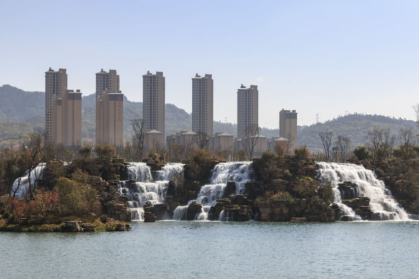 Kunming, China - March 4, 2016: Kunming Waterfall park featuring a 400 meter wide manmade waterfall. Kunming is Yunnan's capital Architecture ASIA Asian  Built Structure City Cityscape Dalí Dianchi Lake Indochina Landmark Lijiang Niulan River Park River Rock - Object Shangrila Sky Skyscraper Tall - High Tourists Travel Destinations Water Waterfall Park Xinhua, Yunnan
