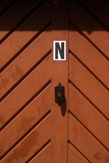 Letter n on brown door