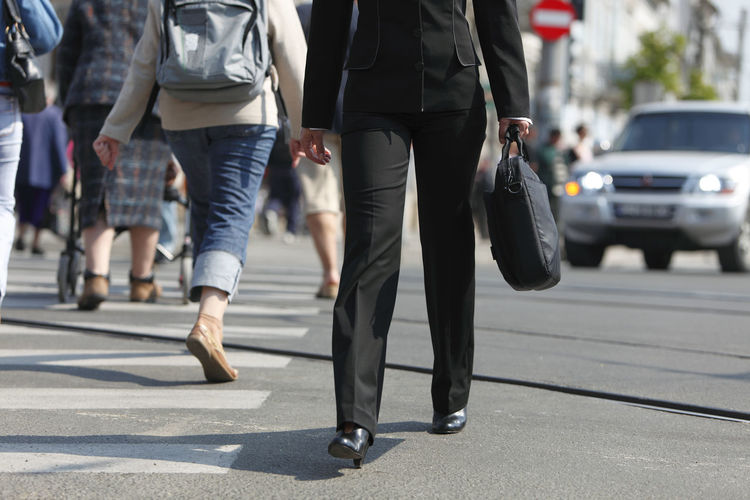 Low section of businesswoman holding bag while walking on city street