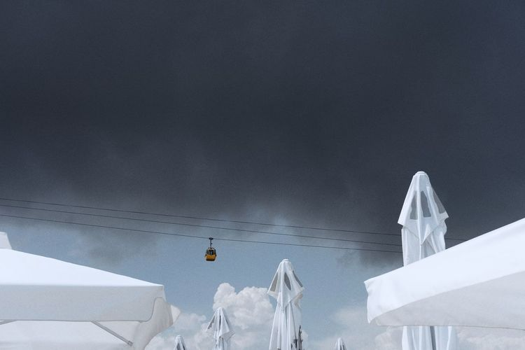 Low Angle View Of Cable Car Over Parasols Against Cloudy Sky
