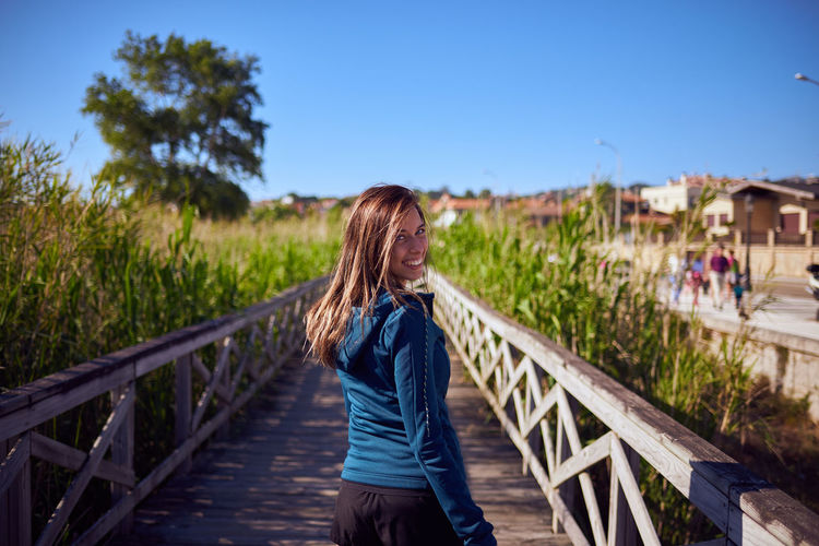 Portrait of young woman walking on footbridge by railing at field