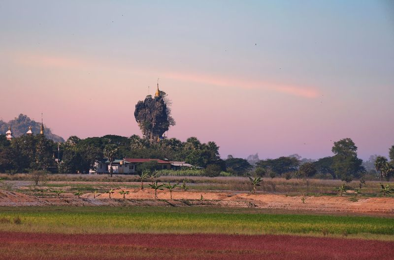 Kyauk Ka Latt Pagoda By Landscape Against Sky During Sunset
