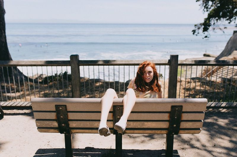 Portrait Of Young Woman Sitting On Bench By Sea