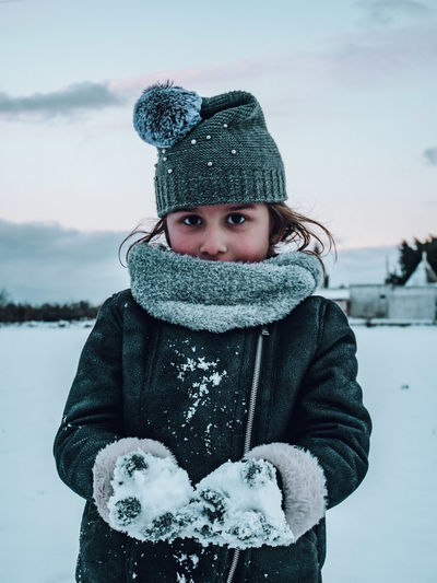 Portrait of girl in warm clothing holding snow during winter