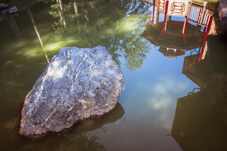 Pagoda Built Structure Chinese Day Lake Lifestyles Nature Outdoors Reflection Rock Rock - Object Solid Standing Water Sunlight Tranquility Tree Water Waterfront