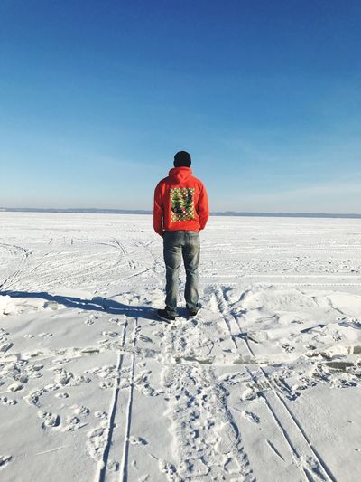 Rear view of man standing on snow covered landscape